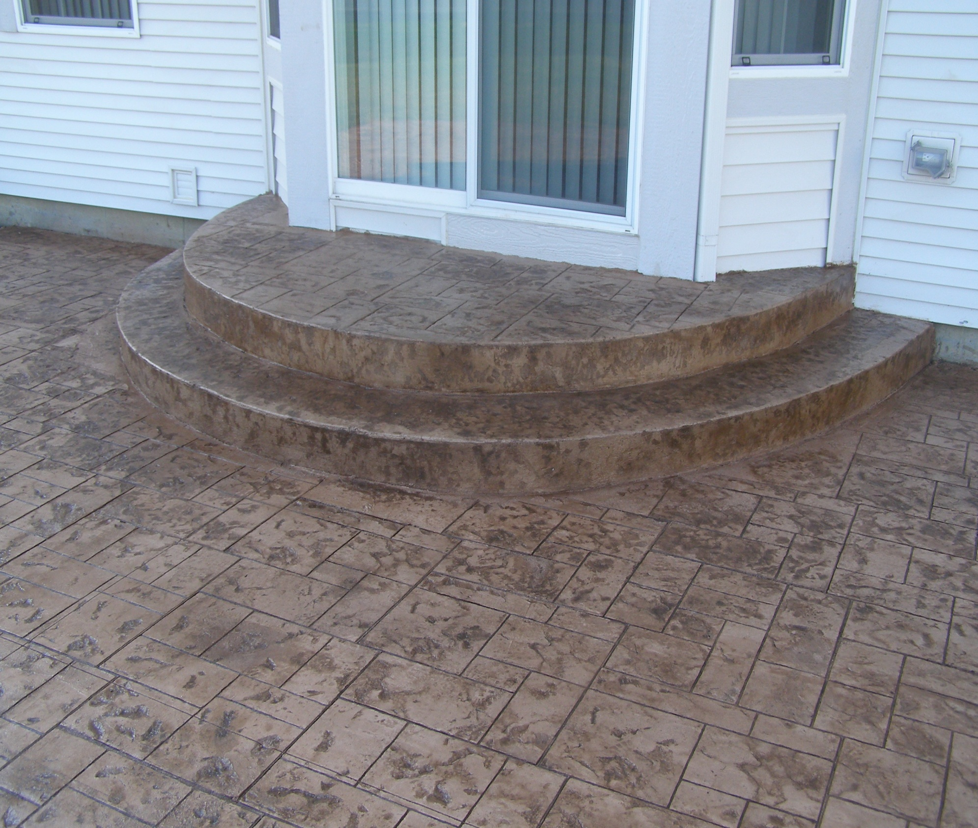 Our Rockford stamped concrete designers can make poured concrete look like brick pavers.